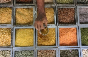 An employee collects lentils from a container inside a grocery store at a residential area in Mumbai