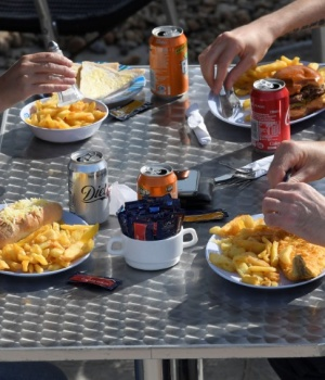 Visitors eat fish and chips and drink soft drinks at a beach cafe in Brighton