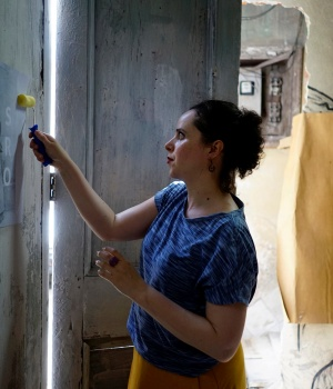 "Brazilian artist Polyanna Morgana, a participant of the ""00Biennial"" hangs a poster on a wall in Havana"
