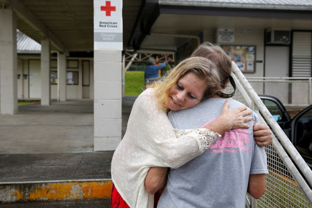 Carolyn McNamara hugs her neighbor Paul Campbell at an evacuation center in Pahoa after moving out of their homes after the Kilauea Volcano erupted, in the Puna community in Hawaii