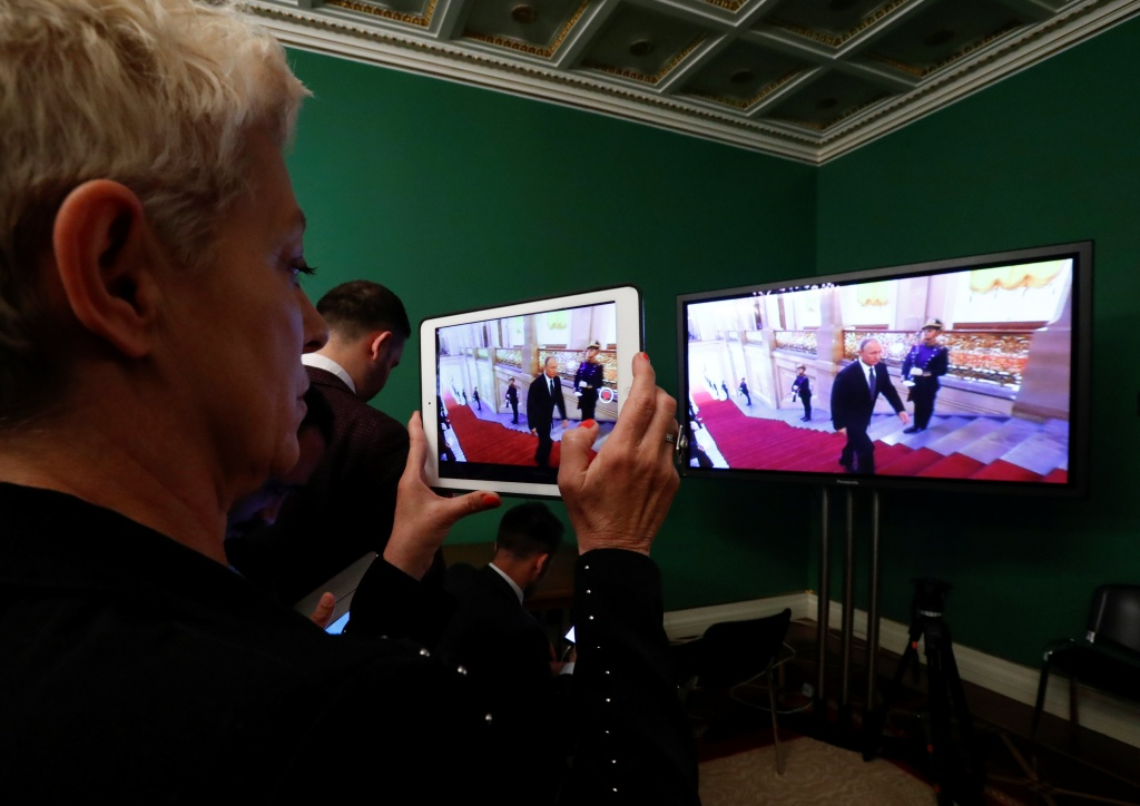 A journalist watches a ceremony to inaugurate Vladimir Putin as President of Russia at a press centre in Moscow