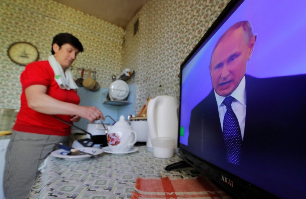 A woman cooks a meal while watching a ceremony to inaugurate Vladimir Putin as President of Russia inside an apartment in Moscow