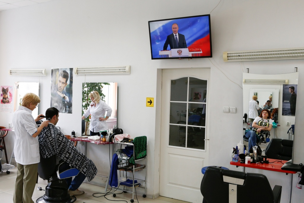 A hairdresser watches a ceremony to inaugurate Vladimir Putin as President of Russia at a hair design salon in Stavropol