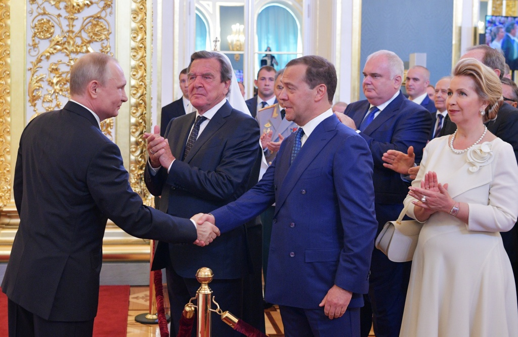 Russian Prime Minister Medvedev and German former Chancellor Schroeder greet Putin, who is sworn as Russian President during an inauguration ceremony in Moscow