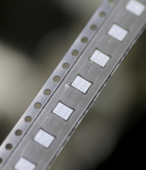 Microchips emerge from a machine onto a roll in the clean room at the UTAC plant in Singapore