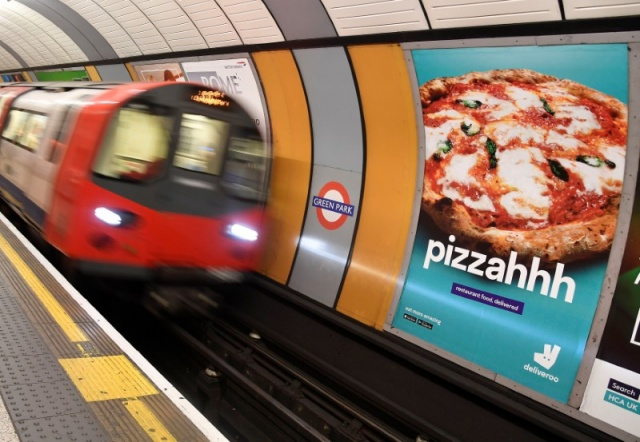 A train passes an advertisement for a food delivery company at Green Park underground station in London Britain