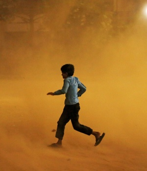 A boy runs for cover during a dust storm in New Delhi