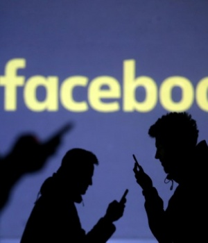 Silhouettes of mobile users are seen next to a screen projection of Facebook logo in this picture illustration