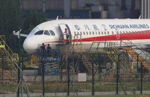 Workers inspect a Sichuan Airlines aircraft that made an emergency landing after a windshield on the cockpit broke off, at an airport in Chengdu