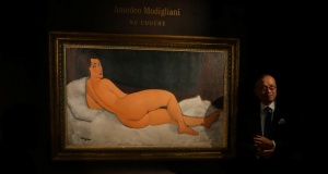"""Kevin Ching, CEO of Sotheby's Asia, stands next to Amedeo Modigliani's """"Nu couche"""", expected to fetch over $150 million (USD) in the New York auction in May, during a preview in Hong Kong"""