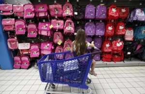 A young girl sitting in a shopping trolley looks at schoolbags in a school stationery section at a supermarket in Nice