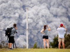 People watch as ash erupt from the Halemaumau crater near the community of Volcano