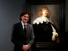 "Dutch art dealer Six poses next to a Rembrandt painting called ""Portrait of a Young Man"" at Hermitage Amsterdam"
