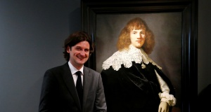 """Dutch art dealer Six poses next to a Rembrandt painting called """"Portrait of a Young Man"""" at Hermitage Amsterdam"""