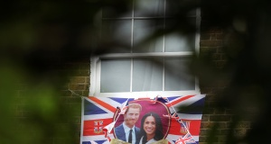 A Union Flag decorated with images of Prince Harry and Meghan Markle hangs from a building outside Windsor Castle ahead of their wedding, in Windsor