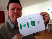 Designer Tonu Kukk holds a paper with a design of Kanepi municipality's flag and coat of arms featuring a cannabis leaf after the municipality council's vote in Polgaste