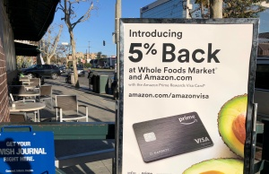 A sign advertising a credit card offering a discount at Whole Foods and Amazon is seen outside a Whole Foods in Los Angeles