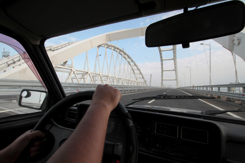 A driver operates a car on a bridge, which was constructed to connect the Russian mainland with the Crimean Peninsula across the Kerch Strait