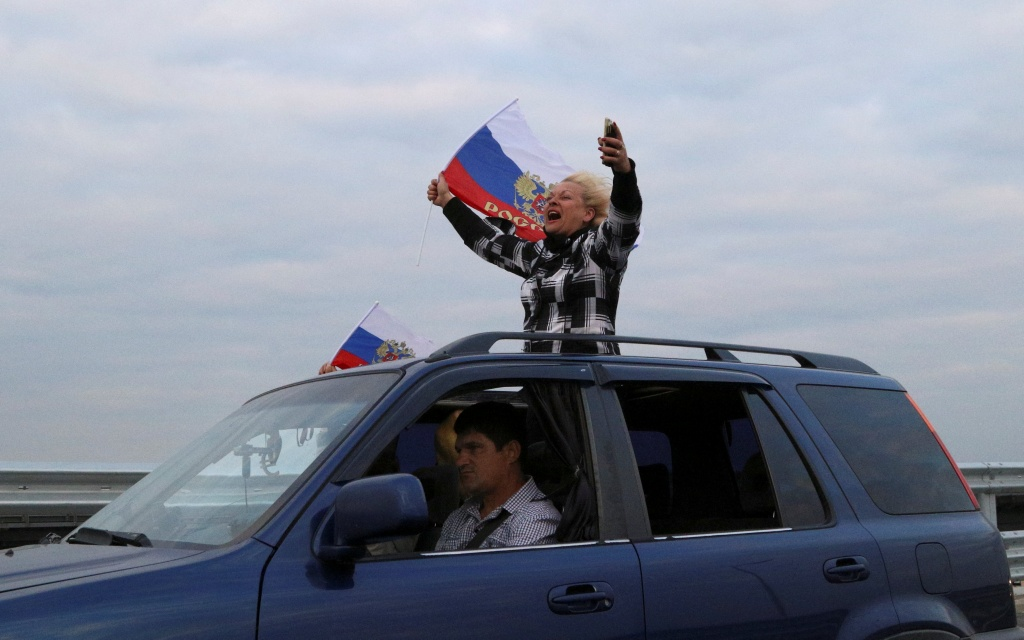 People hold flags with the state coat of arms of Russia as they drive a car along a bridge, which was constructed to connect the Russian mainland with the Crimean Peninsula across the Kerch Strait