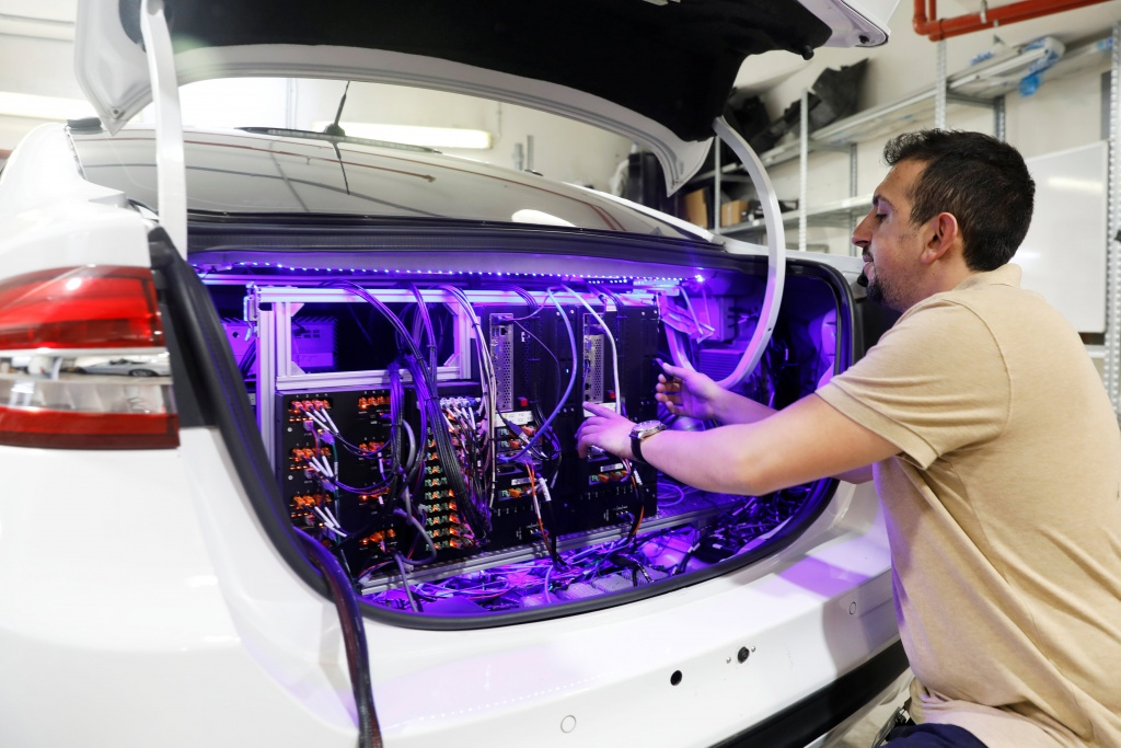 A worker tends to systems in the back of a Mobileye autonomous driving test vehicle, at the Mobileye headquarters in Jerusalem
