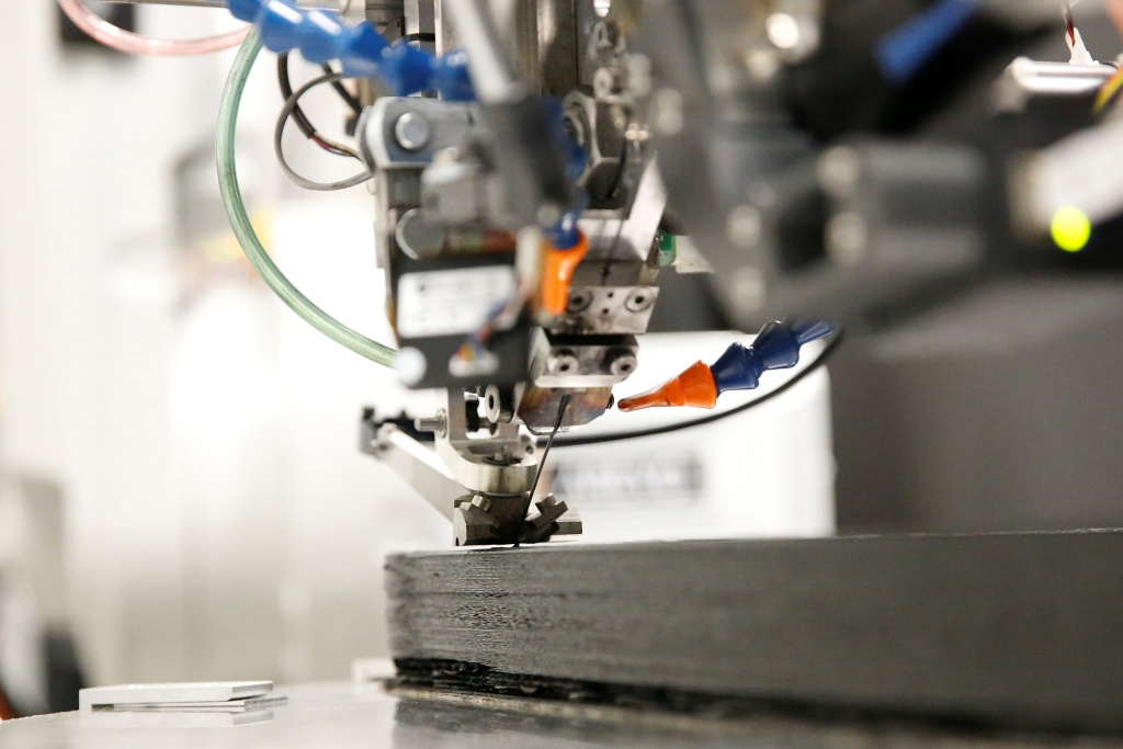 A carbon fiber filament connected to a bicycle frame and a 3D-printing robot is being cut at Arevo Labs in Santa Clara, California