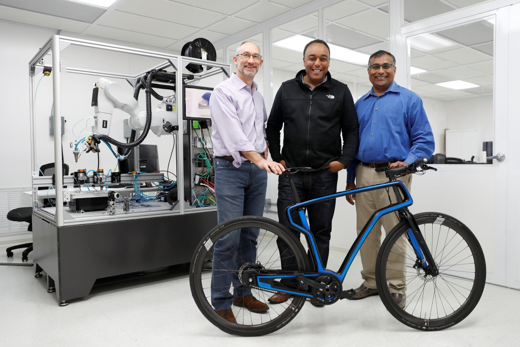 Arevo Labs CEO Jim Miller, CTO Wiener Mondesir, and Chairman and Co-Founder Hemant Bheda stand for a photo with the company's 3D-printed commuter bike in Santa Clara, California