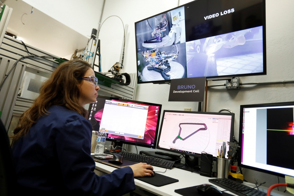 Magda Zydzik, an engineer at Arevo Labs, monitors the progress of a 3D-printing robot as it prints a carbon fiber bicycle frame in Santa Clara, California