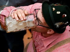 Visitor drinks beer during the opening day of the 184th Oktoberfest in Munich