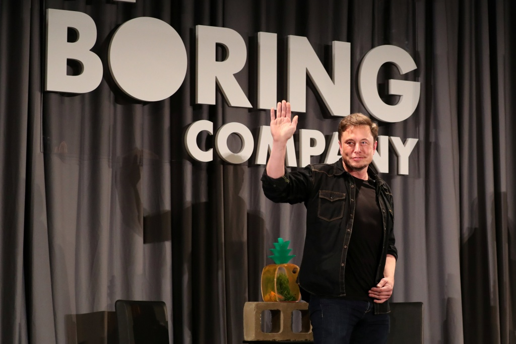 Elon Musk waves after speaking at a Boring Company community meeting in Bel Air, Los Angeles