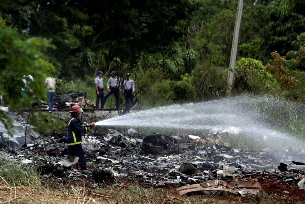 Firefighters work in the wreckage of a Boeing 737 plane that crashed in the agricultural area of Boyeros
