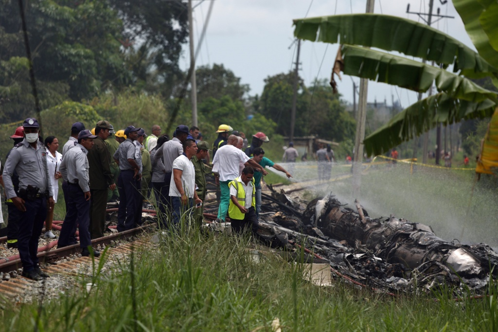 Rescue team members work in the wreckage of a Boeing 737 plane that crashed in the agricultural area of Boyeros