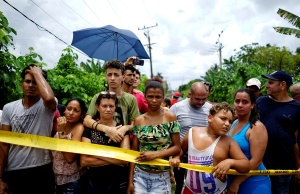 People look on near of the wreckage of a Boeing 737 plane that crashed in the agricultural area in Boyeros,