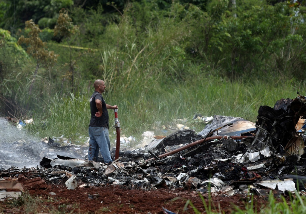 A rescue team member looks on while working in the wreckage of a Boeing 737 plane that crashed in the agricultural area of Boyeros
