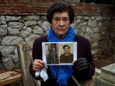 Carmen Benito Alcantarilla holds pictures of her uncle Valentin Alcantarilla Mercado who was shot in 1940 by forces of dictator Francisco Franco in Guadalajara's cemetery