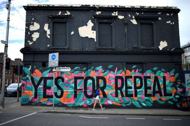 A woman walks past a Pro-Choice mural on the side of a building ahead of a 25th May referendum on abortion law