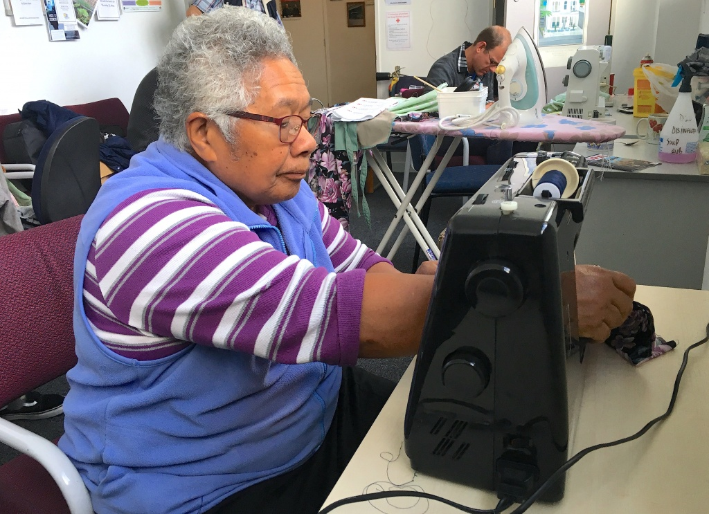 Sister Josefa uses a sewing machine as she teaches sewing at the Compassion Soup Kitchen in Wellington