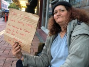 A woman, known only as Margaret and claiming to be homeless, holds a sign as she begs for money on a main street in central Wellington