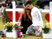 Mourners pray at a makeshift memorial left in memory of the victims killed in a shooting at Santa Fe High School in Santa Fe