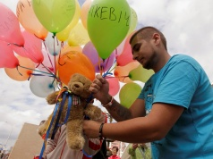 A man attaches a teddy bear to balloons during an opposition picket in central Minsk
