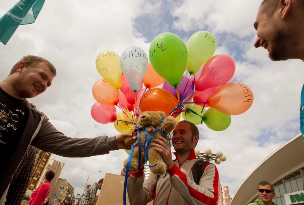 Men attach a teddy bear to balloons during an opposition picket in central Minsk