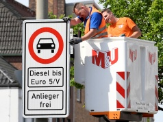 Traffic signs which ban diesel cars are installed by workers at the Max-Brauer Allee in downtown Hamburg