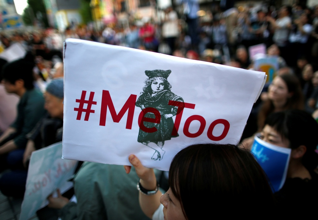 "A protester raises a placard reading ""#MeToo"" during a rally against harassment in Tokyo"