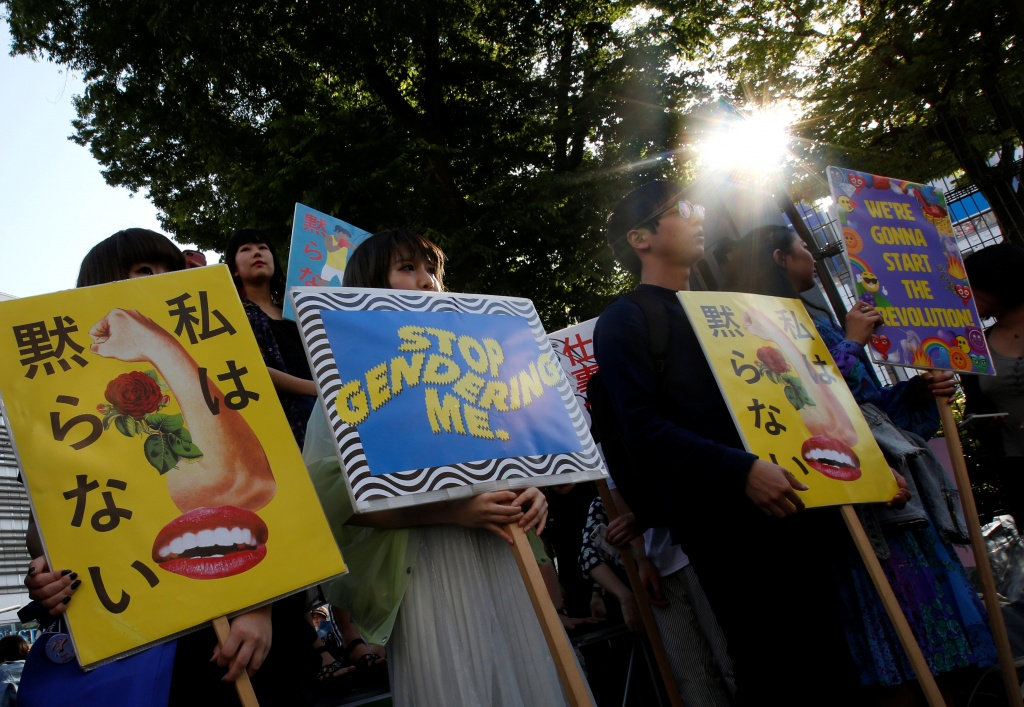Protesters hold placards during a rally against harassment in Tokyo
