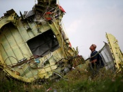 A Malaysian air crash investigator inspects the crash site of Malaysia Airlines Flight MH17, near the village of Hrabove (Grabovo) in Donetsk region