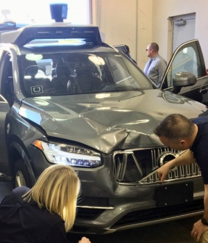 NTSB investigators examine a self-driving Uber vehicle involved in a fatal accident in Tempe