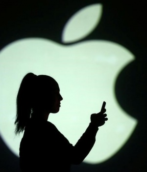 Silhouette of mobile user is seen next to a screen projection of Apple logo in this picture illustration