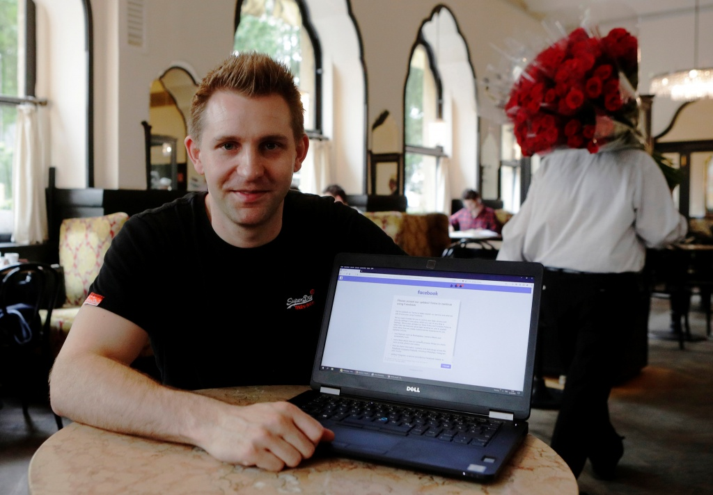 Austrian lawyer and privacy activist Schrems displays his Facebook account's updated terms page during a Reuters interview in Vienna