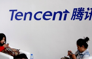 Visitors use phones underneath of logo of Tencent at Global Mobile Internet Conference in Beijing