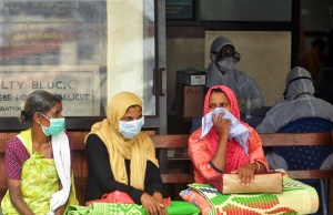 People wear masks as they wait outside a casualty ward at a hospital in Kozhikode