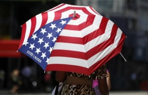 A woman shades herself from the sun with an umbrella as she walks down 34th Street in New York J